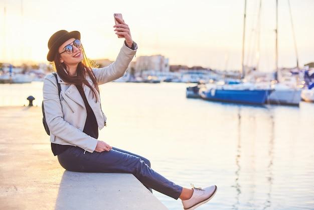 Vrij jonge vrouw in zwarte hoedenzitting op een pijler met een telefoon bij een zeehaven