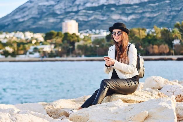 Vrij jonge vrouw in zwarte hoedenzitting op een rots met een celtelefoon