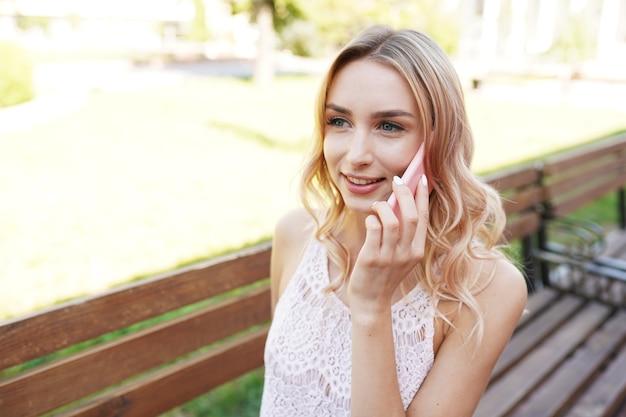Vrij jonge vrouw met behulp van witte mobiele telefoon thuis lachend