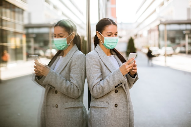 Vrij jonge vrouw met beschermend gezichtsmasker op straat