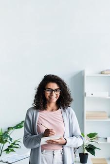 Vrij jonge vrouw met blocnote in bureau