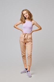 Vrij jonge vrouw met blond slordig haar in mouwloos onderhemd en broek met handen op taille