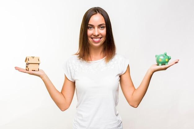 Vrij jonge vrouw met een huisje en een spaarvarken