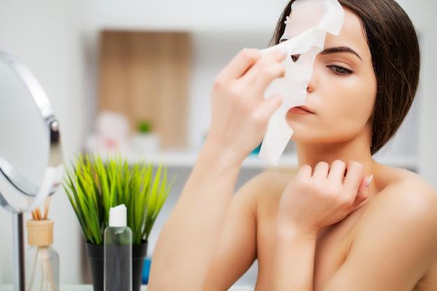 Vrij jonge vrouw met gezichtsmasker in badkamers
