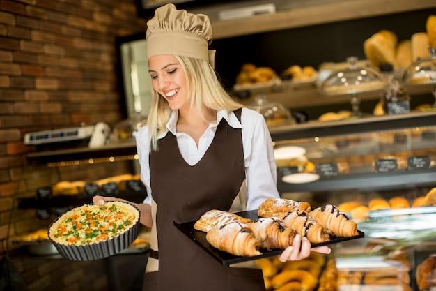 Vrij jonge vrouw met quiche lotharingen in de bakkerij