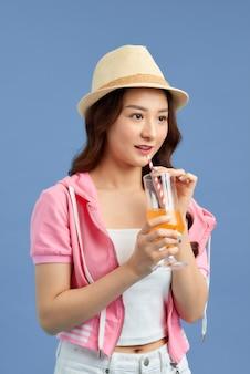 Vrij jonge vrouw met sappig fruit op kleurenachtergrond
