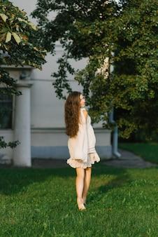 Vrij jonge vrouw of meisje in een vliegende lichte jurk loopt