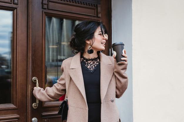 Vrij jonge vrouw op de stadsstraat met mobiele telefoon en koffie