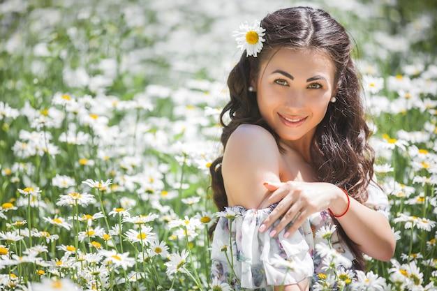 Vrij jonge vrouw op het kamillegebied. mooi meisje met bloemen