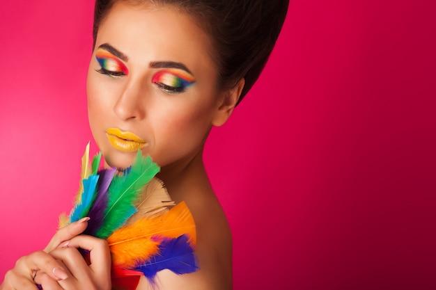 Vrij jonge vrouw op kleurrijke achtergrondholdingsveren. het portret van aantrekkelijk meisje met creatief maakt omhoog