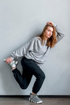 Vrij jonge vrouw poseren tegen grijze muur