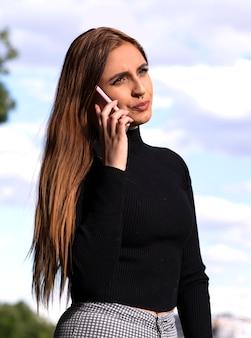 Vrij jonge vrouw praat op haar telefoon terwijl haar gezicht serieus is