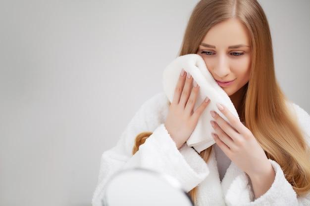Vrij jonge vrouw veegt het gezicht handdoek na het douchen af