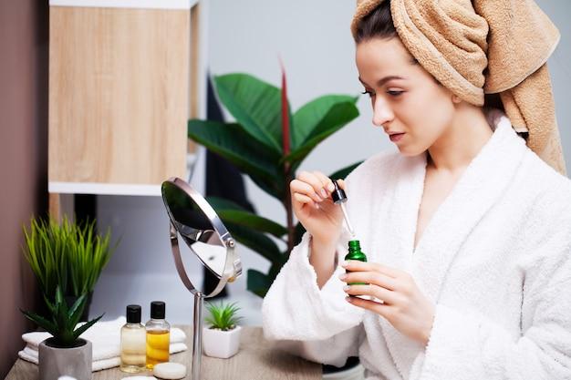 Vrij jonge vrouw zet make-up op het gezicht in de badkamer