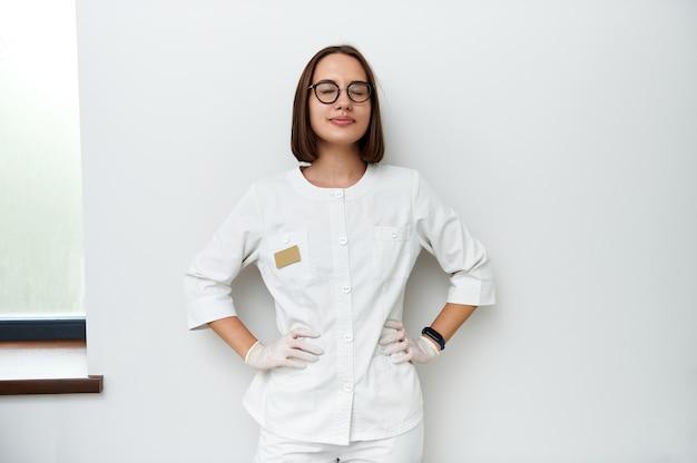 Vrij jonge vrouwelijke arts met gesloten ogen die tegen witte muur in medische kliniek leunen. professioneel portret. internationale doktersdag