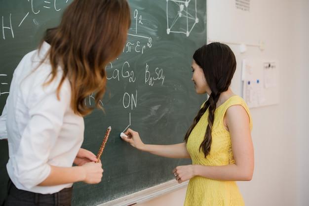 Vrij jonge vrouwelijke student die op het bordbord schrijven tijdens een chemieklasse