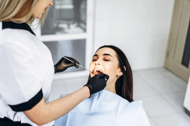 Vrij jonge vrouwelijke tandarts die onderzoek en behandeling voor jonge vrouwelijke patiënt in tandkliniek maken.
