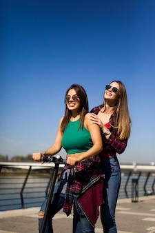Vrij jonge vrouwelijke vrienden die een elektrische autoped in de straat berijden