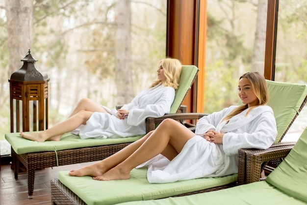 Vrij jonge vrouwen die door het binnen zwembad bij de winter ontspannen