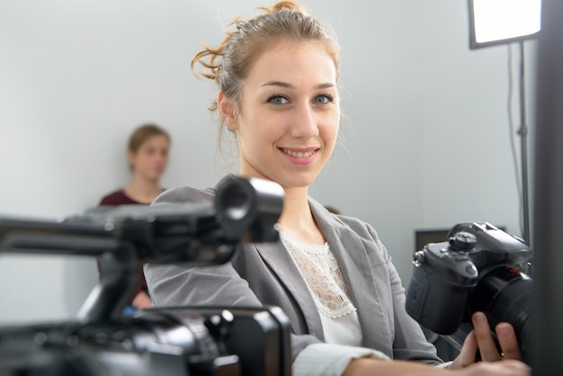 Vrij jonge vrouwenfotograaf met camera in bureau