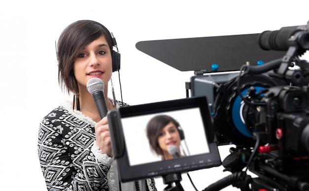 Vrij jonge vrouwenjournalist die rapport in televisiestudio op wit voorleggen