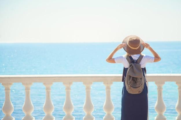 Vrij jonge vrouwentoerist die zich door het overzees op een zonnige dag bevindt