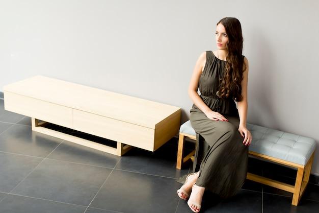 Vrij jonge vrouwenzitting op bank in de moderne ruimte door grijze muur