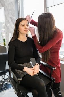 Vrij jonge wenkbrauwmeester zette verf op modellengezicht