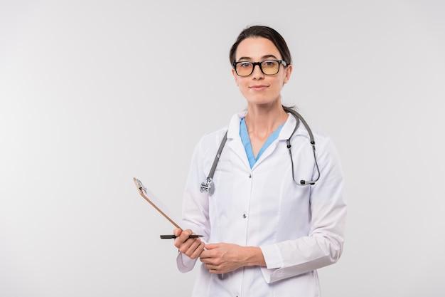 Vrij jonge zelfverzekerde clinicus in het klembord van de whitecoatholding met document terwijl hij geïsoleerd voor camera staat