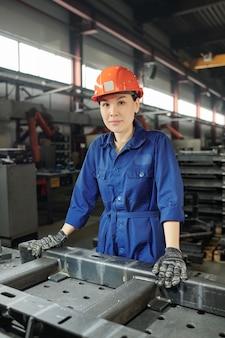 Vrij jonge zelfverzekerde fabrieksarbeider in blauw uniform, handschoenen en helm poseren