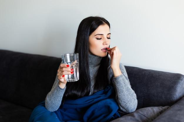 Vrij jonge zieke vrouw die een ochtend na pil en een glas water thuis houdt