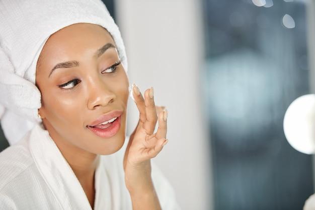 Vrij jonge zwarte die hydraterende gezichtslotion toepast na het nemen van een douche in de ochtend