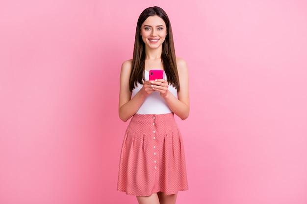Vrij kalm brunette meisje houdt telefoon chatbericht vast