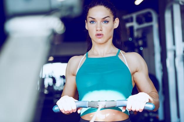 Vrij kaukasisch brunette met paardenstaart en in sportkleding die krachtoefening voor biceps en triceps doen. bodybuilding voor vrouwenconcept.