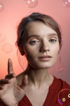 Vrij kaukasisch meisje in rood overhemd met halslijn die camera op roze achtergrond onderzoekt. zeepbellen vliegen om haar heen