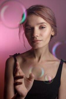 Vrij kaukasisch meisje in zwarte kleding met halslijn die camera op roze achtergrond onderzoekt. zeepbellen vliegen om haar heen