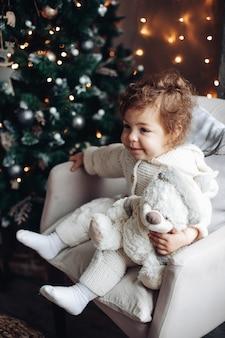 Vrij kaukasisch meisje met krullend haar zit in de buurt van een grote mooie kerstboom en ontspant