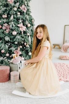 Vrij kaukasisch schoolmeisje zittend op een hobbelpaard in de buurt van versierde kerstboom