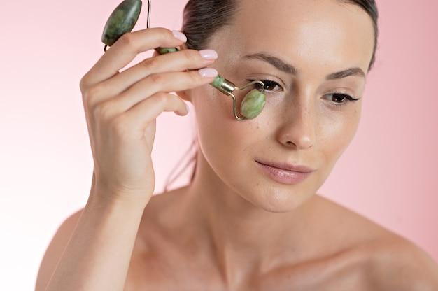 Vrij kaukasische vrouw die huid onder ogen masseert met schoonheidsrol over roze achtergrond. vrouwelijk model dat gezichtsprocedures doet voor het opheffen van effect. rituelen tegen veroudering.