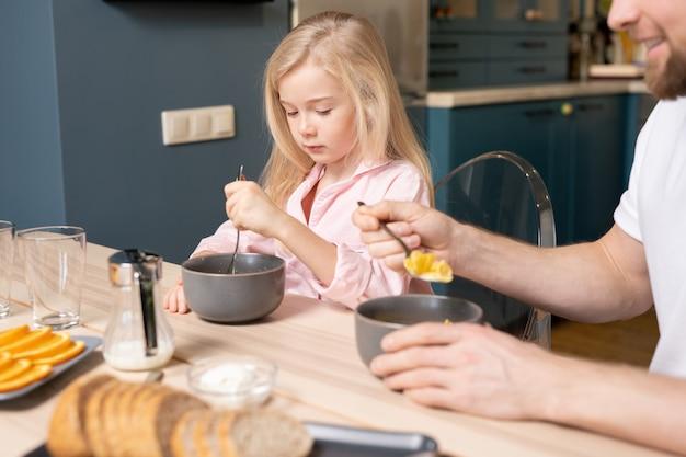 Vrij klein blond meisje en haar vader zitten door houten tafel in de keuken en eten muesli met melk voor het ontbijt in de ochtend