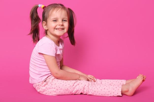 Vrij klein kind met twee paardenstaarten en veel kleurrijke scrunchies zit op de vloer en blij om gefotografeerd te worden in fotostudio. schattige kind glimlacht. kinderen en jeugdconcept.
