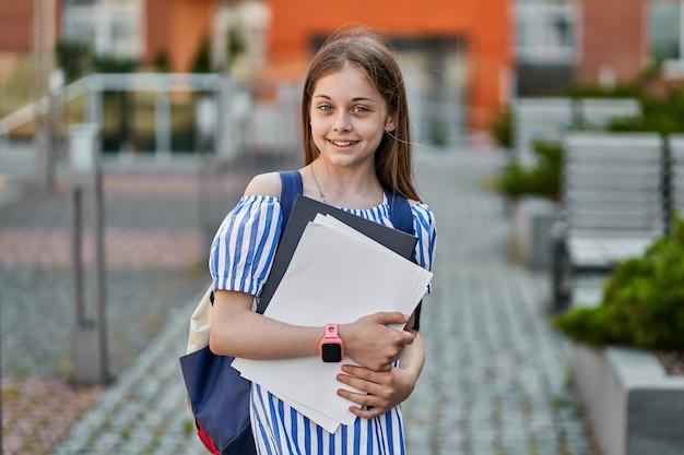 Vrij klein leerling meisje met rugzak en boeken in de buurt van school.