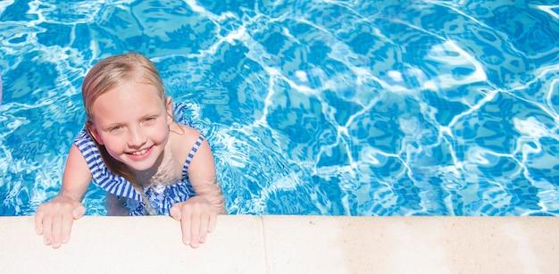 Vrij klein meisje in zwembad, zomervakanties.