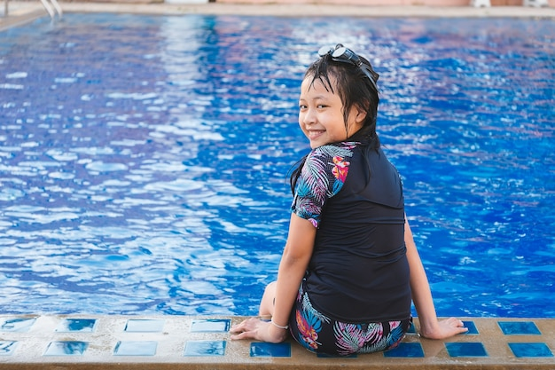 Vrij klein meisje, zittend aan het zwembad met een glimlach en gelukkig in de zomer