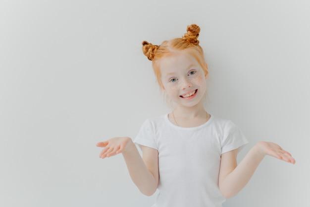 Vrij klein vrouwelijk kind met dubbele foxy-broodjes spreidt de handpalmen zijwaarts
