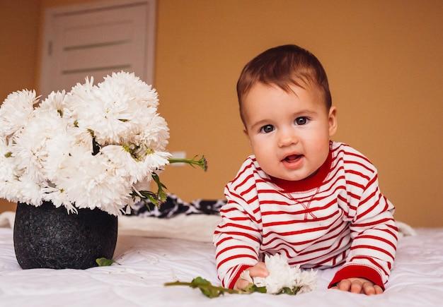 Vrij kleine jongen in gestripte pyjama speelt met margrieten op het bed