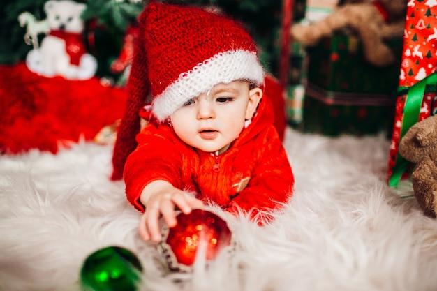 Vrij kleine jongen in rood kostuum vóór een kerstboom