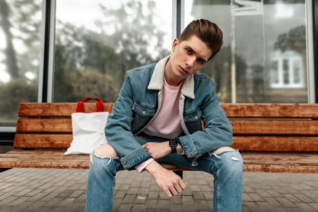 Vrij knappe jongeman in mode roze t-shirt in modieuze blauwe spijkerjas in jeans met stijlvolle witte stof shopper zitten in de buurt van glazen wand in straat. aardige vent in trendy jeugdkleren geniet ervan.