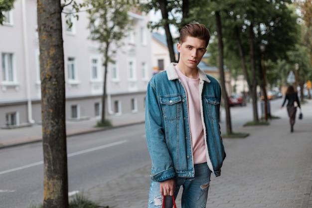 Vrij knappe jongeman met stijlvol kapsel in mode roze t-shirt in modieus blauw spijkerjack in vintage jeans loopt in de buurt van de weg op straat. aardige vent in trendy jeugdkleren geniet ervan.