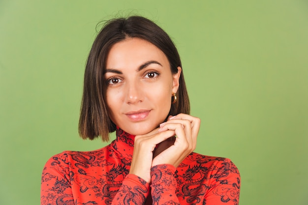 Vrij kort haar vrouw met lichte make-up gouden oorbellen rode china draak gedrukte blouse op groen, positieve emoties, zelfverzekerde glimlach